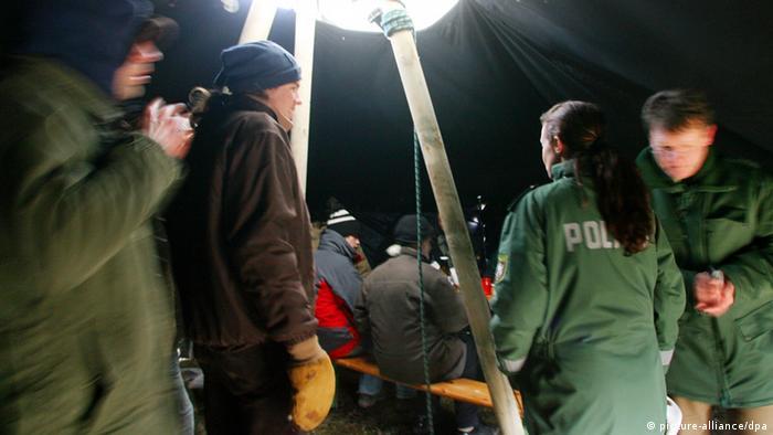 Mitglieder des Bundes für Umwelt und Naturschutz (BUND) und zwei Polizisten unterhalten sich im Frühstückszelt.  Foto: Roland Weihrauch dpa/lnw +++(c) dpa - Bildfunk+++