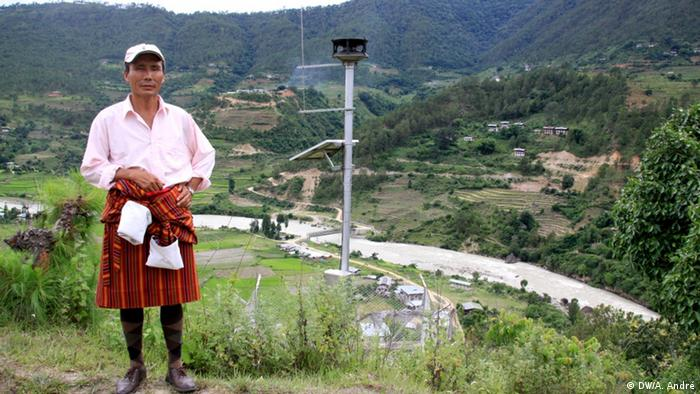 Tauchu, the Tewang Gup or local leader of the area that includes Samdinkha and several other villages, poses with the siren tower above the village. The siren tower is one of 14 along the river Puna Tsang Chu and is part of an early warning system in case of a glacial lake outburst flood (GLOF). Copyright: DW/Aletta André