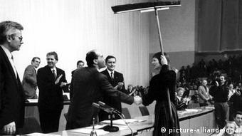 In a black-and-white photograph, a male politician wearing a suit raises a large broom above his head