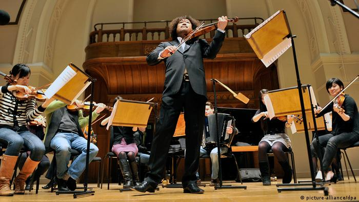 Japan's popular violinist Taro Hakase (C) plays a charity concert for the victims of Japan's earthquake and Tsunami at Cadogan Hall in London, Britain, 18 March 2011. (Photo: EPA/ANDY RAIN)