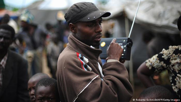 A man listens to news on the radio as he stands next to improvised shelters that people fleeing violence have setup in front of a UN peacekeepers base in the outskirts of the North Kivu town of Kiwanja on November 07, 2008 (photo: ROBERTO SCHMIDT/AFP/Getty Images).