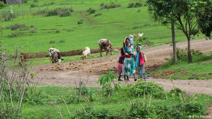 Woman and children return from the fields in Awra Amba