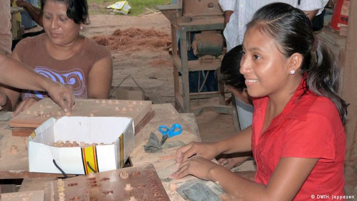 Women making wooden toys in a workshop in San Andres, El Peten, Guatemala 