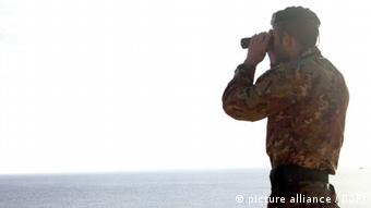 Italy, Lampedusa island (Agrigento) - October 8, 2013 Refugees tragedy. An Italian army soldier scans the sea with a binoculars at Isola dei Conigli, Lampedusa island.