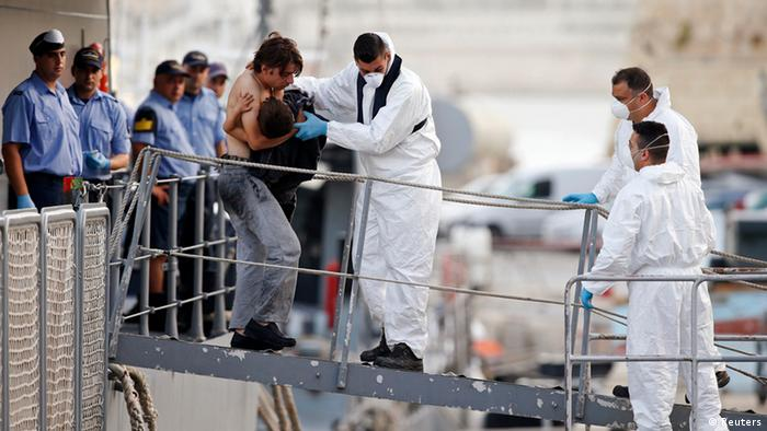 A rescued migrant carries his child as he disembarks from an Armed Forces of Malta (AFM) ship at the AFM Maritime Squadron base at Haywharf in Valletta's Grand Harbour October 12, 2013. Dozens of people died on Friday when a boat carrying around 250 migrants capsized between Sicily and Tunisia, in the second such shipwreck this month, the Italian coastguard said. 147 survivors, believed to all be Syrians, arrived in Malta on Saturday morning, according to local media. REUTERS/Darrin Zammit Lupi (MALTA - Tags: SOCIETY IMMIGRATION DISASTER MARITIME) MALTA OUT. NO COMMERCIAL OR EDITORIAL SALES IN MALTA