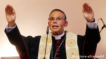 A bishop wearing black robes raises both hands into the air in a religious gesture while speaking into a microphone.