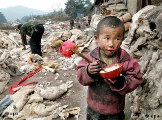 Ein chinesisches Kind isst Reis, sein Vater sucht auf einer Müllhalde in Guiyang nach Verwertbarem (Quelle: dpa)