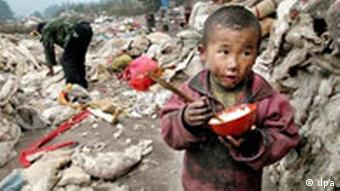 A child eats food from a rubbish heap