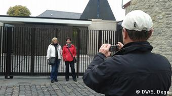 Two casually-dressed women pose before a black, rolling gate while a man wearing a white hat and blue jacket photographs them. Photo: Stefan Dege/DW