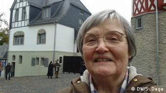 An elderly woman wearing glasses smiles at the camera with a white house with dark slate roofing in the background. Photo: Stefan Dege/DW