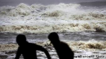 Indian people run for shelter following a cyclone warning at the Bay of Bengal coast in Gopalpur beach in Ganjam district about 200 kilometers (125 miles) from the eastern Indian city Bhubaneswar, India, Saturday, Oct. 12, 2013. Hundreds of thousands of people living along India's eastern coastline were taking shelter Saturday from a massive, powerful cyclone Phailin that was set to reach land packing destructive winds and heavy rains. (AP Photo/Biswaranjan Rout)