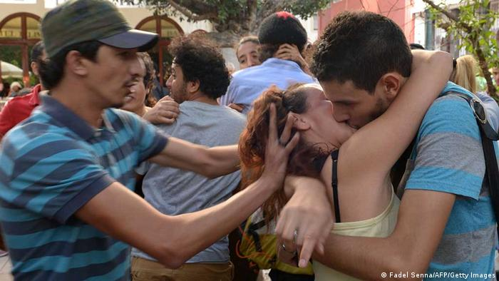 A man tries to stop a couple from taking part in a 'kiss-in' outside the parliament in the Moroccan capital Rabat on October 12, 2013. The event was organised by Moroccan activists in protest at the arrest and trial of three teenagers for 'violating public decency' after posting photos of two of them kissing on Facebook. The offending couple, a boy and a girl aged 15 and 14, and their 15-year-old male friend who took the photos outside their school in the northern town of Nador, were arrested last week. AFP PHOTO/FADEL SENNA (Photo credit should read FADEL SENNA/AFP/Getty Images) - eingestellt von gri