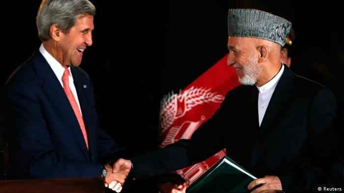 Afghanistan's President Hamid Karzai (R) shakes hands with US Secretary of State John Kerry after a news conference in Kabul October 12, 2013. REUTERS/Mohammad Ismail