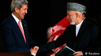 Afghanistan's President Hamid Karzai shakes hands with U.S. Secretary of State John Kerry REUTERS/Mohammad Ismail
