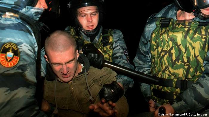 Polizisten führen Mann nach rechtsradikalen Krawallen auf Moskauer Markt ab (Foto: AFP)