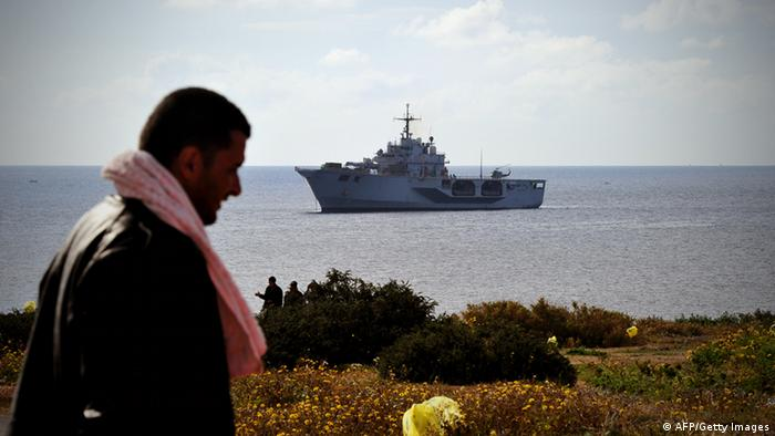 A Tunisian would-be immigrant walks past the Italian navy ship San Marco in the harbor of the Italian island of Lampedusa ALBERTO PIZZOLI/AFP/Getty Images