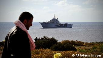 A Tunisian would-be immigrant walks past the Italian navy ship San Marco in the harbour of the Italian island of Lampedusa on March 30, 2011. Tension is rising on the Italian Mediterranean island of Lampedusa over the thousands of immigrants arriving from Libya, with patience running out as the numbers grow. More than 2,000 people have fled Libya by boat to Malta and Italy, but none among them appear to be Libyans according to a spokeswoman from the UN High Commissioner for Refugees (UNHCR). AFP PHOTO / ALBERTO PIZZOLI (Photo credit should read ALBERTO PIZZOLI/AFP/Getty Images)
