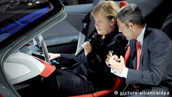 Angela Merkel sits at the wheel of a concept car.