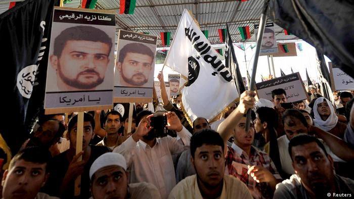 People hold posters of senior al Qaeda figure Abu Anas al-Liby (L) during a demonstration over his capture by U.S. authorities, in Benghazi October 11, 2013. Libyan citizen Al-Liby, whose real name is Nazih al-Ragye, is a suspect in the 1998 bombings of U.S. embassies in Kenya and Tanzania that killed 224 civilians. Since his capture in Tripoli last week, he has been held aboard a Navy ship in the Mediterranean where an elite team of American interrogators is questioning him. REUTERS/Esam Omran Al-Fetori (LIBYA - Tags: POLITICS CRIME LAW CIVIL UNREST)