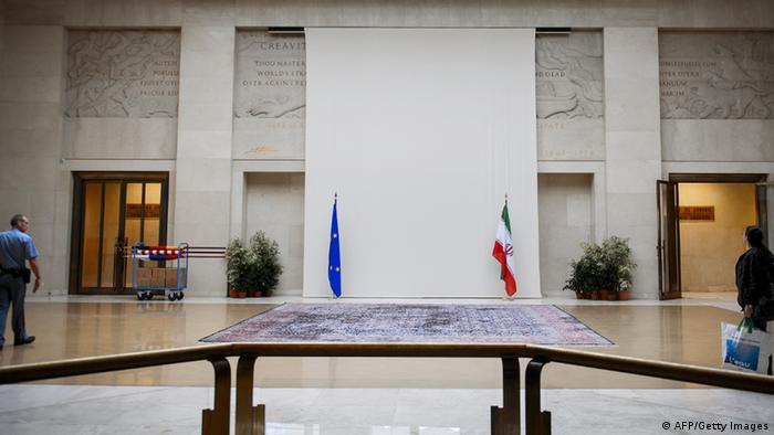 A security guard walks near a sculpture of a naked man covered up by a curtain behind the European and Iranian flags on October 14, 2013 at the United Nations' Geneva offices, ahead of fresh talks between world powers and Iran on its controversial nuclear programme. The cover-up of the marble man and his clearly visible penis was first reported by the Swiss newspaper Tribune de Geneve, which claimed that the aim was to avoid offending the Islamic republic's delegation talks. Swiss officials declined to address the newspaper's claim, and told AFP that the aim was to provide a neutral backdrop at the entrance to the meeting hall. AFP PHOTO / FABRICE COFFRINI (Photo credit should read FABRICE COFFRINI/AFP/Getty Images)
