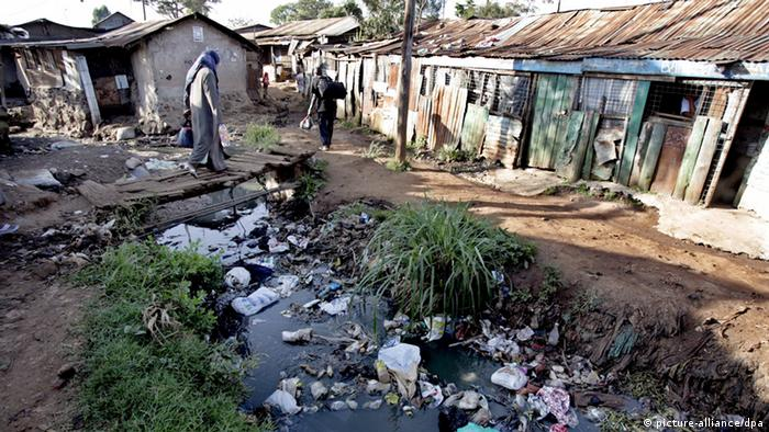 A Kenyan woman walks across a small wooden bridge in the slum of Kibera in Kenyan's capital Nairobi. The water is dirty and full of rubbish, the houses shacks. EPA/STEPHEN MORRISON +++(c) dpa - Bildfunk+++