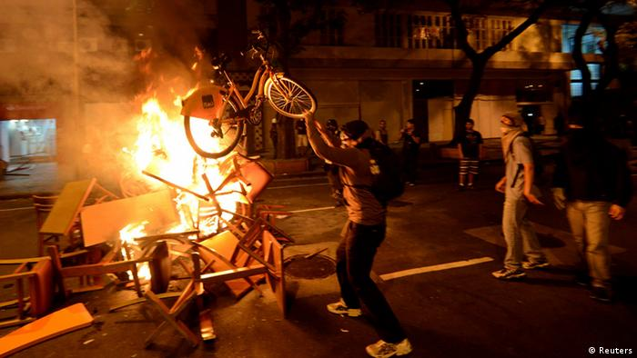 An anti-government protester throws a bike onto a fire during a clash with riot police after a protest supporting a teachers' strike in Rio de Janeiro October 15, 2013. The protest is to demand changes in the public state and municipal education system. REUTERS/Lucas Landau (BRAZIL - Tags: CIVIL UNREST POLITICS EDUCATION)