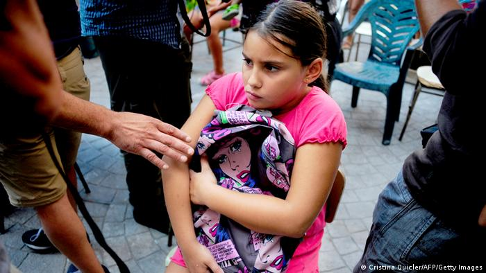 Die Kinder sind die leitragende der spanischen Wirtschaftskrise: A young girl holds her new school bag during a distribution of school supplies organized by activists of Andalusian Union of Workers (SAT) in Sevilla on September 8, 2013. On August 30, more than 200 activists of the left-wing group SAT filled 10 carts with school materials, notebooks, pens, pencils, erasers and dictionaries, and took them from a supermarket to redistribute goods to families affected by the recession. All the families have moved in to an abandoned building project -renamed 'Corrala Utopia' by its residents- after they were evicted from their homes when they failed to pay their rent or mortgage. AFP PHOTO / CRISTINA QUICLER (Photo credit should read CRISTINA QUICLER/AFP/Getty Images)