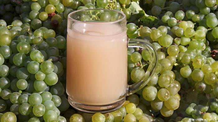 A glass of Federweisser against a backdrop of grapes