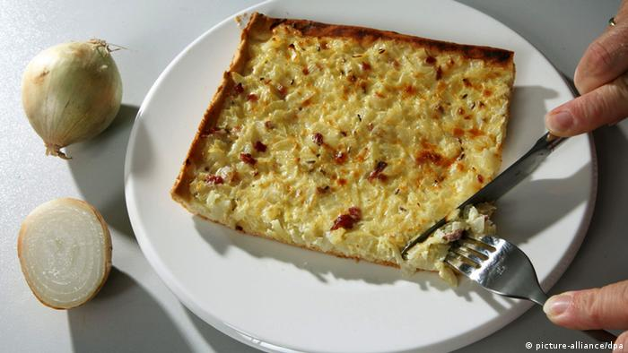 A slice of Zwiebelkuchen on a plate about to be eaten