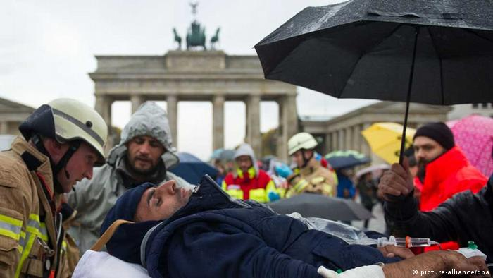 A refugee is taken away on a gurney in front of the Brandenburg Gate. (Photo: Ole Spata/dpa)