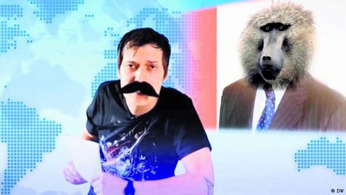 junger Moderator im Nachrichten-Set vor einem Foto mit einem Pavian