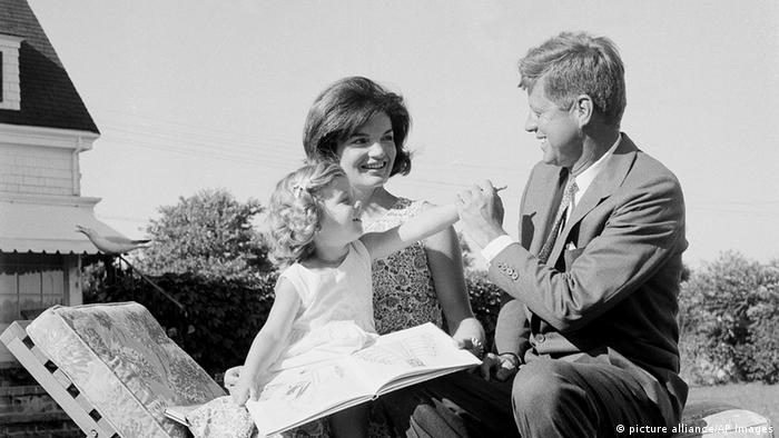 Caroline Kennedy, 2 1/2, reaches for her father, Sen. John F. Kennedy as her mother Jacqueline holds her at their home at Hyannis Port, Mass., July 21, 1960. The senator from Massachusetts is mapping out his campaign for the presidency. (AP Photo)