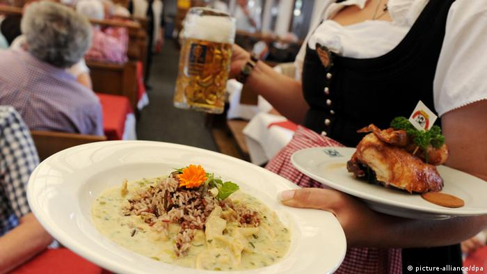 A waitress carrying plates at Oktoberfest (photo: picture alliance/dpa)