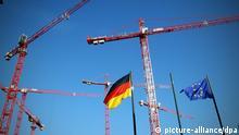 ARCHIV - Die europäische und die deutsche Flagge ist am 12.10.2012 im Regierungsviertel in Berlin zwischen Baukränen zu sehen. Die deutsche Wirtschaft verliert in der Schuldenkrise zunächst an Fahrt, der Arbeitsmarkt bleibt aber voraussichtlich trotzdem stabil. Foto: Wolfgang Kumm/dpa +++(c) dpa - Bildfunk+++