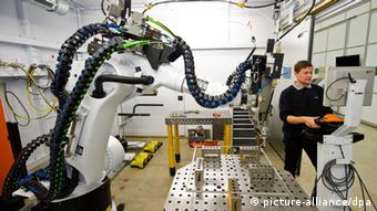 Ein Mitarbeiter stellt am 15.10.2013 in Ditzingen (Baden-Württemberg) beim Maschinenbauer Trumpf eine Roboterzelle ein. Das Familienunternehmen Trumpf kauft einen chinesischen Werkzeugmaschinenhersteller. Foto: Daniel Bockwoldt/dpa +++(c) dpa - Bildfunk+++