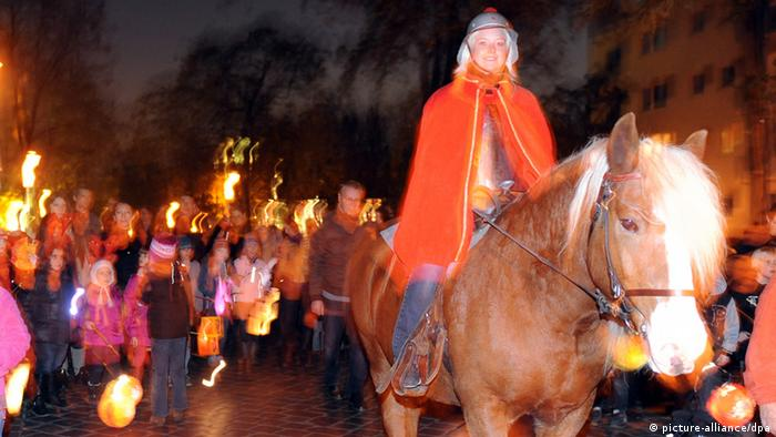 A woman dressed up as St. Martin on a horse leading a group of children with lanterns. (Photo: Britta Pedersen dpa/lbn)