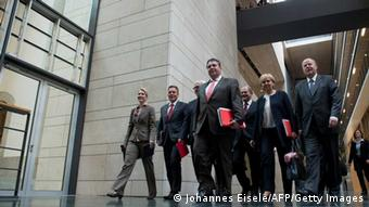 Sigmar Gabriel (C), leader of the Social Democratic Party (SPD), and party members (L-R) Manuela Schwesig, Thomas Oppermann, Frank-Walter Steinmeier (slightly hidden), Gabriel, Olaf Scholz, Hannelore Kraft and Peer Steinbrueck are on their way to a meet members of the conservative CDU/CSU union for a third round of exploratory talks on October 17, 2013 in Berlin. German Chancellor Angela Merkel faces a new headache after her search for a coalition partner turned into a one-horse race, forcing her to haggle with the emboldened Social Democrats. The Greens politely bowed out of further talks with Merkel's conservatives overnight, citing irreconcilable differences, leaving the Social Democrats (SPD) as Merkel's only potential partner, which will allow them to drive a harder bargain. AFP PHOTO / JOHANNES EISELE (Photo credit should read JOHANNES EISELE/AFP/Getty Images)