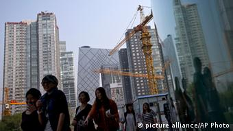 Women walk past a construction site and office buildings at the Central Business District during their lunch break in Beijing, China Tuesday, Oct. 8, 2013. Chinese President Xi Jinping sought Monday to reassure Asian business and political leaders that his country only aspires to peace and that he is confident its economic growth will remain robust despite a recent slowdown. (AP Photo/Andy Wong)