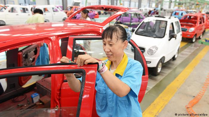 Chinese workers assemble cars
