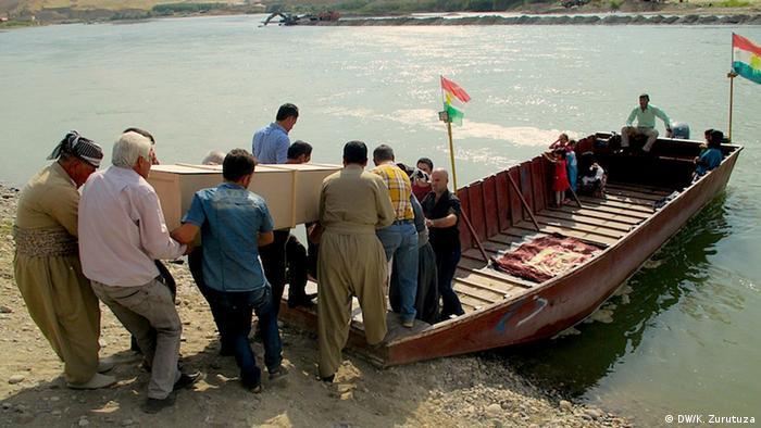 A group loads a coffin onto a boat over the Khabur River.  (Photo: Karlos Zurutuza /DW)