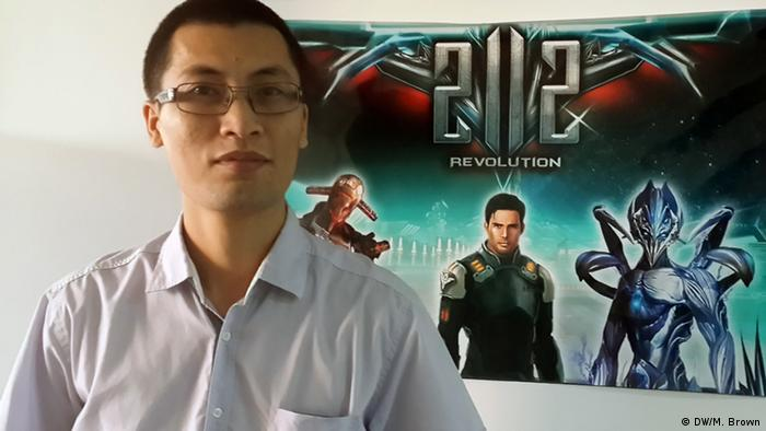 Nguyen Tuan Huy poses beside a poster of his latest online game 2112.