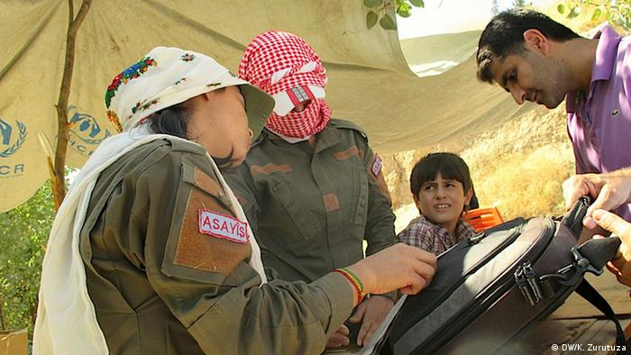 Two female members of the Kurdish police check the refugees' luggage on the Syrian side of the border.  (Photo: Karlos Zurutuza / DW)
