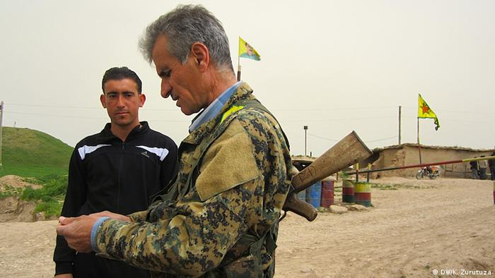 A Kurdish YPG-soldier checks the documents of a Syrian refugee between Syria and Iraq.  (Photo: Karlos Zurutuza / DW)