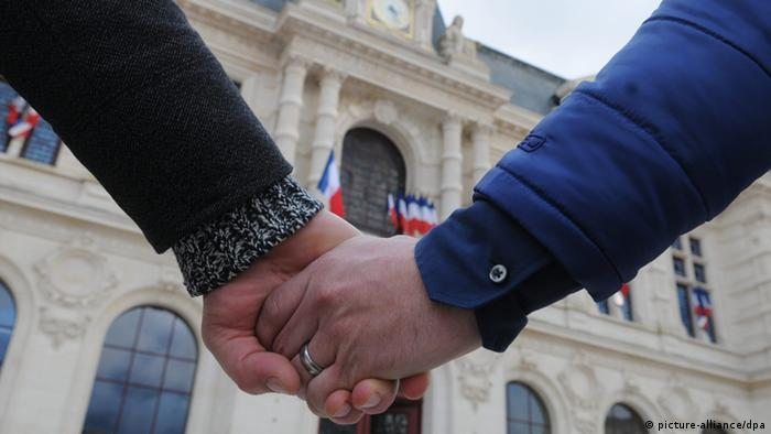 Two hands clasp one another in front of a stone, European building. Photo: PATRICK LAVAUD