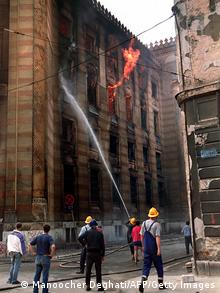 Firefighters douse flames inside the National Library in Sarajevo 26 August 1992. Thousands of books and historical documents are housed in the building which was hit by shells during artillery duels in the capital. An international conference in London met 26 August to resolve the conflict. (Photo credit should read MANOOCHER DEGHATI/AFP/Getty Images)