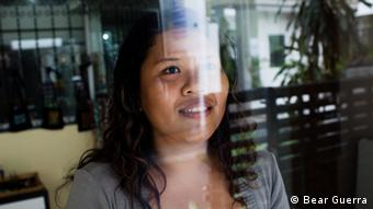 Mint, a former prostitute, smiles with the reflection of a glass window over her face.