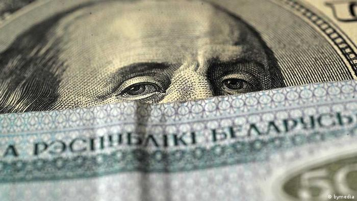Белорусские деньги на фоне 100-долларовой купюры
