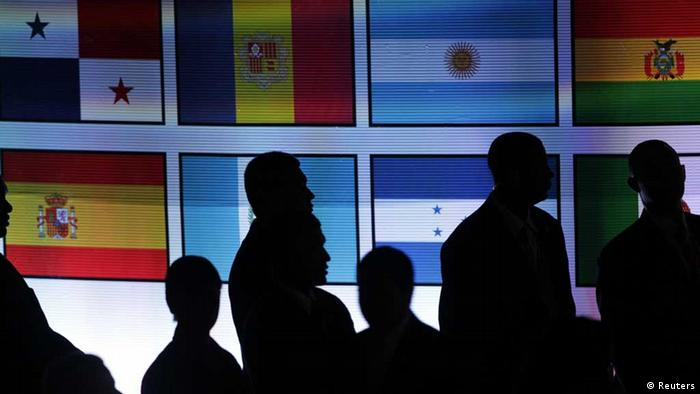 Attendees stand in front of a screen with Ibero-American flags on display before the inauguration of the Ibero-American Summit in Panama City October 18, 2013. Leaders from Latin American countries, Spain and Portugal are attending the summit from October 18-19. REUTERS/Jorge Cabrera (PANAMA - Tags: POLITICS) // eingestellt von se