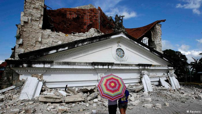 Residents look at a collapsed Holy Trinity parish church at Loay, Bohol after an earthquake struck central Philippines October 17, 2013.