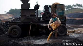 An Indian child works at a coal depot
